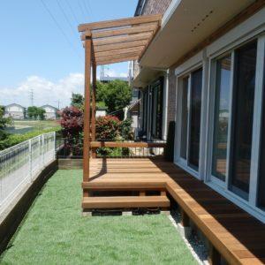 屋根付パーゴラ・ベンチの付いたウッドデッキと人工芝の庭