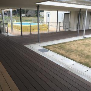 保育施設と庭をつなぐ開放的な渡り廊下と樹脂木フェンス